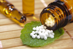 alternative medicine with homeopathic globules on leaf
