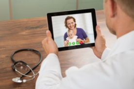 Doctor Talking To Patient Over Laptop Video Chat