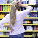 blond woman shopping in the supermarket choosing a body care product
