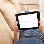 Man relaxing with tablet pc, laying on sofa