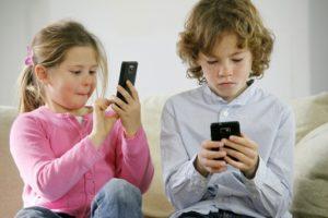 due bambini sul divano con smartphone