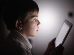 bambino al buio con smartphone