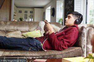 ragazzo steso sul divano con smartphone